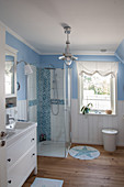 Shower and wainscoting in blue-and-white maritime bathroom