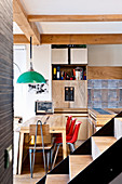 Dining table and green pendant lamp in open-plan kitchen with furnishings made from recycled materials