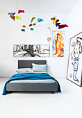 Grey bed in corner of room decorated with modern artworks