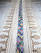 Strip of modern, multicoloured, geometric tiles on antique mosaic floor