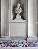 Modern, geometric tiles below antique bust flanked by columns