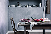 Apples and vintage enamel bowl on wooden table in country-house kitchen