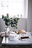 Branches of eucalyptus in vase next to enamel saucepan on marble board in kitchen