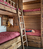 Rustic bunk beds made from reclaimed wood with red gingham bed linen