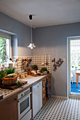 Pale blue walls and blue-and-white patterned tiles in country-house kitchen