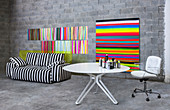 Swivel chair at round table next to monochrome striped sofa and multicoloured striped artworks