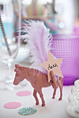 Name tag and feather on toy horse painted pink