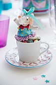 Circus elephant in cup on table set for birthday party