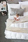 Girl sitting on bed surrounded by knitted blankets and cushions in natural shades