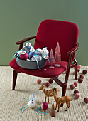 Numbered Christmas tree baubles on red upholstered chair