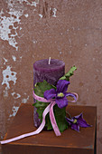 Purple pillar candle decorated with leaf, clematis flower and velvet ribbon