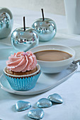 Cupcake and cup of coffee on table set in pale blue and pink