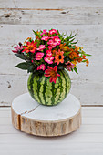 Summer bouquet in vase made from hollowed-out watermelon