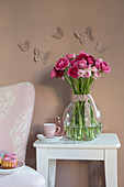 Vase of ranunculus below butterfly decorations on brown wall