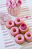 Gebäck mit rosafarbenem Zuckerguss und Ranunkeln