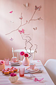 Romantically set table in front of pink wall decorated with butterflies