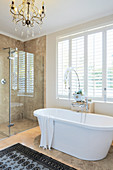 Free-standing bathtub and glazed shower area in elegant bathroom
