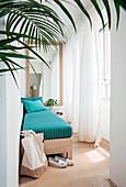 Holzbett mit türkisfarbener Auflage in schmalem lichtdurchfluteten Raum eines Strandhauses