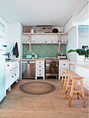 Blue-and-green mosaic-tiled splashback and white kitchen cabinets in light-flooded kitchen