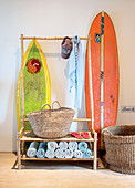 Surfboards stored behind coat rack made from bamboo poles