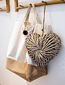 Cloth bag and love-heart decoration hanging from bamboo coat rack
