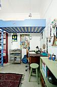 Jugendzimmer mit Schreibtisch unter blauem Hochbett