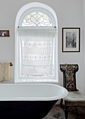 Embroidered, antique chair and lace curtain in arched window in vintage-style bathroom