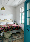 Open blue door leading into guest room with decorative handmade quilt on bed