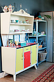 Multicoloured retro dresser next to industrial-style metal shelves