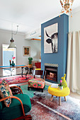 Living room in colourful eclectic style with blue-painted chimney breast