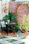 Vintage-style wrought iron garden furniture on gravel terrace in corner of garden