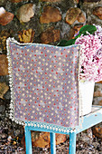 Chair with pretty loose cover made from lilac floral fabric and lace trim