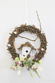 Wreath decorated with twigs, spring flowers and ornamental bird box