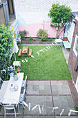 Terrace area and lawn surrounded by brightly painted walls in courtyard garden