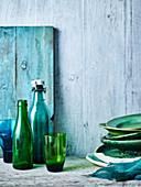 Stilleben mit grün-blauen Tellern, Gläsern und Flaschen