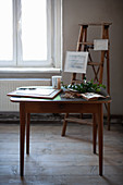 Vintage-style accessories on old stepladder and wooden table on wooden floor