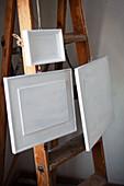 Weiß bemalte Bilder im Rahmen hängen an alter Holzleiter