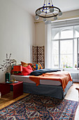 Double bed with colourful bed linen in bedroom
