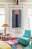 Pale blue designer rocking chair, classic pendant lamp, side table and wall hanging in living room