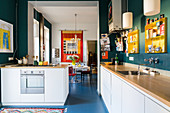 Kitchen counter with white cabinets, petrol-blue wall and dining room with colourful wall hanging in background