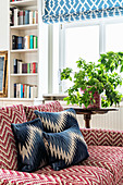 Sofa with zigzag pattern and houseplant on side table in front of window