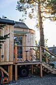 Wooden tiny house on stilts with exterior steps and small veranda