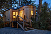 Wooden tiny house on stilts with exterior steps and small veranda at twilight illuminated from within