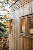 Round extension of tiny house with multiple small windows and wood-clad exterior