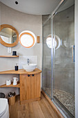 Wooden washstand and glass shower doors in bathroom in round extension of tiny house