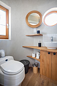 Wooden washstand, porthole window and toilet in bathroom of tiny house