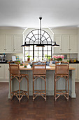 Black, metal, arched window and cane-backed barstools in kitchen