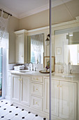 White cupboards and black-and-white tiled floor in elegant bathroom