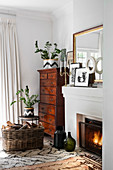 Antique tallboy next to fireplace decorated with mirror, pictures, sculpture and candlesticks