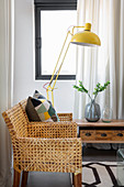 Yellow standard lamp next to cane chair